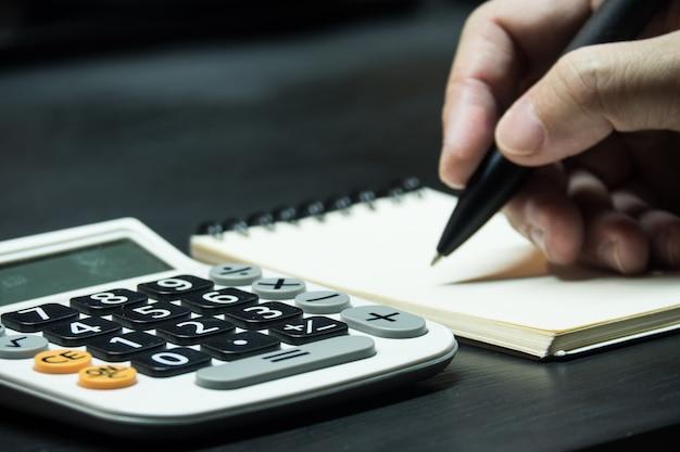Chiuda sulla mano dell'uomo con la penna e la carta per appunti con il calcolatore sul fondo di legno dello scrittorio.
