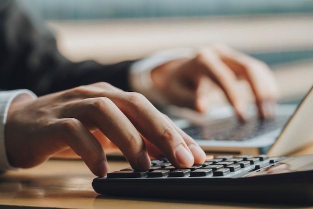 Chiuda sulla mano dell'uomo d'affari facendo uso del calcolatore e del computer portatile nell'ufficio. concetto di finanza