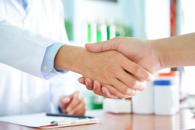 Chiuda sulla mano dell'uomo del farmacista che agita al contatore con il cliente paziente
