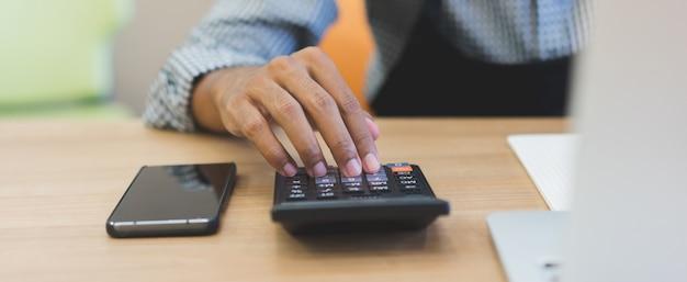 Chiuda sulla mano dell'uomo del proprietario di affari facendo uso del calcolatore per lavorare all'ufficio