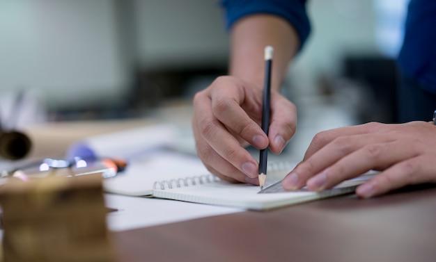 Chiuda sulla mano dell'uomo dell'architetto facendo uso della progettazione di piano del disegno a matita dei lavori di costruzione sul libro di schizzo