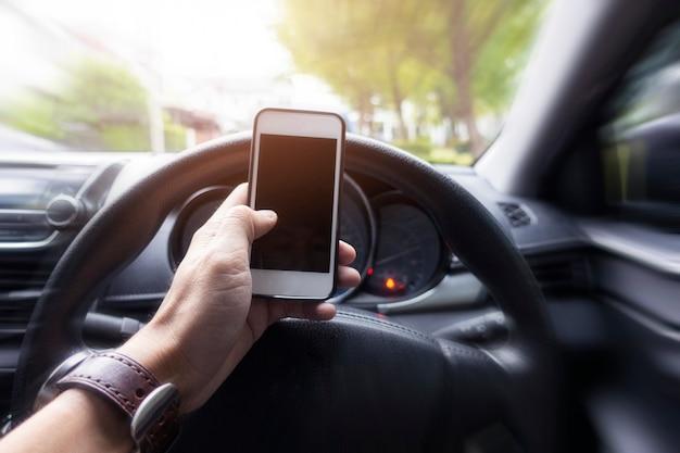Chiuda sulla mano dell'uomo facendo uso dello smart phone mentre sta conducendo l'automobile