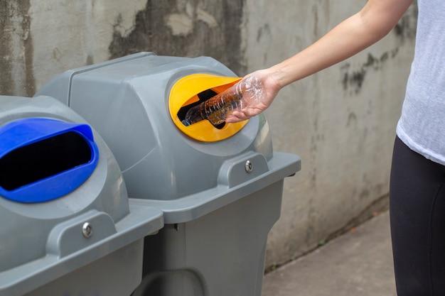 Chiuda sulla mano della donna che getta la goccia di plastica vuota della bottiglia nel recipiente di riciclaggio