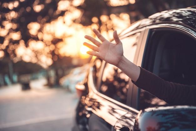 Chiuda sulla mano della donna che si rilassa e che gode del viaggio stradale e del tramonto.