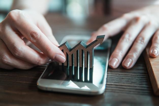 Chiuda sulla mano della donna che sistema il simbolo di legno di crescita.