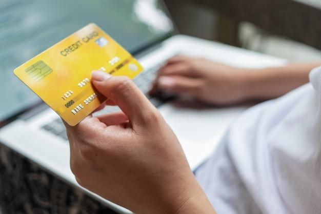 Chiuda sulla mano della donna che tiene la carta di credito e che per mezzo del computer portatile