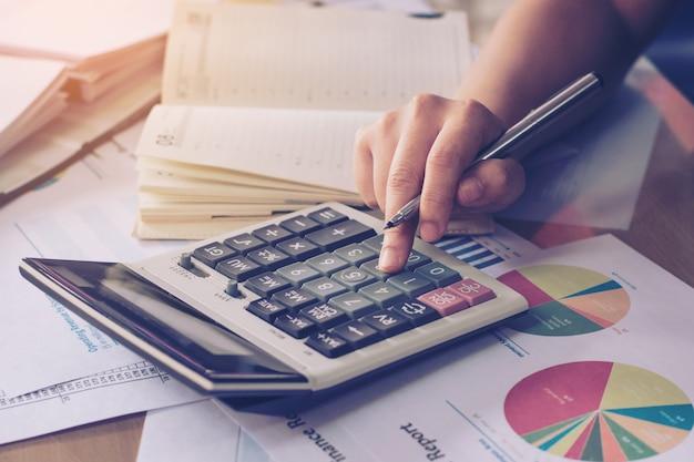 Chiuda sulla mano della donna facendo uso del calcolatore e la scrittura fa la nota con calcola alla scrivania.