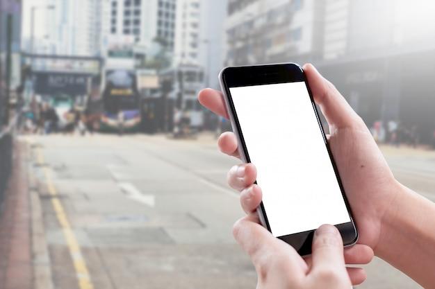 Chiuda sulla mano della donna facendo uso di uno smart phone con lo schermo in bianco a hong kong street.