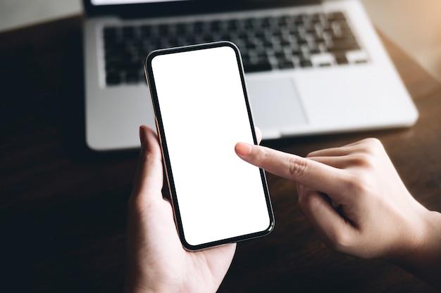 Chiuda sulla mano della donna facendo uso di uno smart phone con lo schermo in bianco alla caffetteria.