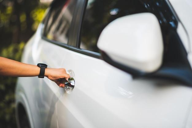 Chiuda sulla mano della donna sulla maniglia per l'apertura della porta di automobile per guidare