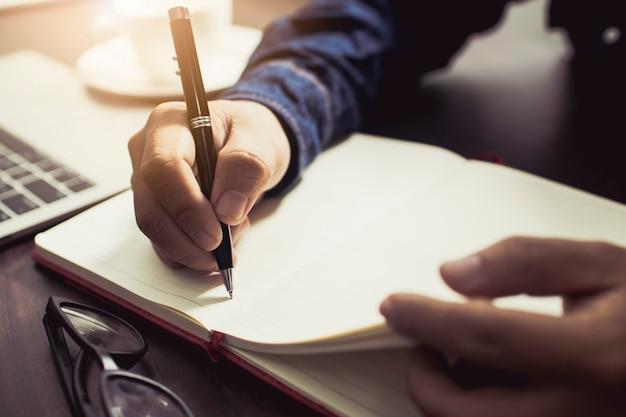 Chiuda sulla mano della gente che indossa il diario di scrittura del tralicco e le informazioni della nota sul tavolo di lavoro a casa