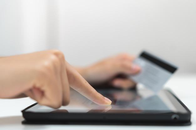 Chiuda sulla mano della persona che compera nel cellulare e che paga via la banca di internet.