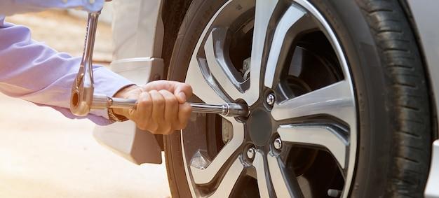 Chiuda sulla mano delle mani del meccanico facendo uso della chiave per cambiare una gomma di automobile. concetti di supporto, riparazione e servizi di assicurazione auto.