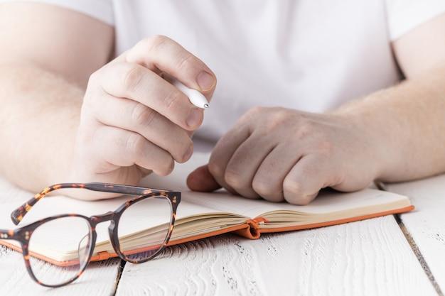 Chiuda sulla mano delle note di scrittura dello studente dentro al taccuino
