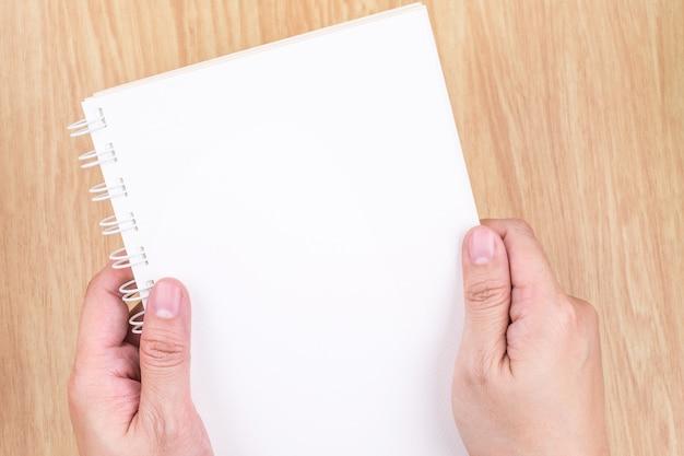 Chiuda sulla mano due che tiene il libro aperto bianco vuoto sopra lo scrittorio di legno