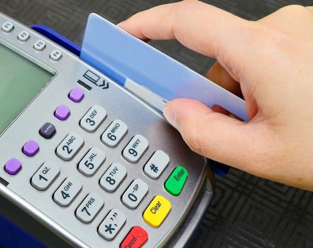Chiuda sulla mano facendo uso della spazzatrice della carta di credito per pagare, comprare e vendere i prodotti & assista il concetto.