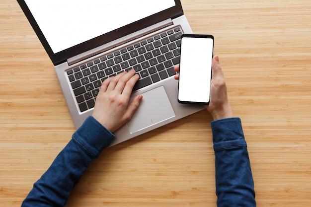 Chiuda sulla mano facendo uso dello schermo bianco del computer portatile e del telefono sulla tavola dell'area di lavoro.