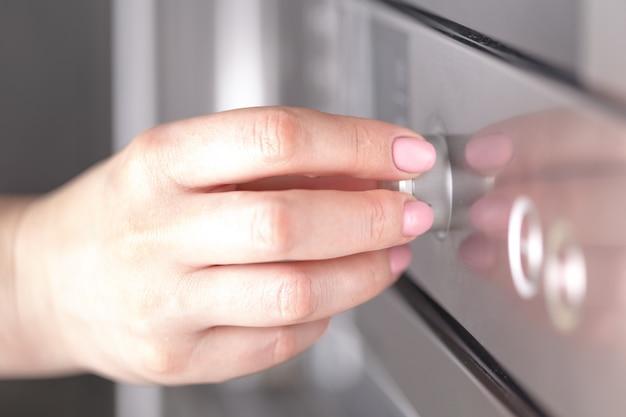 Chiuda sulla mano femminile mentre utilizza il microonde nella sua cucina