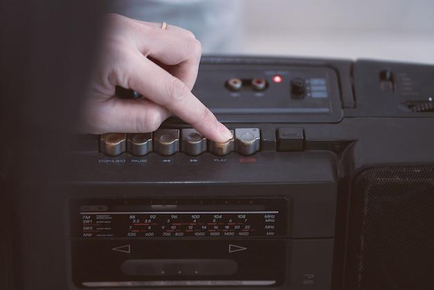 Chiuda sulla mano per scegliere il riproduttore di cassette del nastro. stile vintage