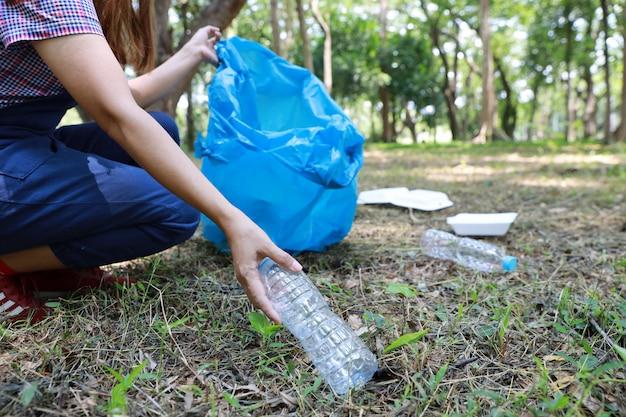 Chiuda sulla mano turistica volontaria che pulisce i detriti di plastica e dell'immondizia sulla foresta sporca nella grande borsa blu