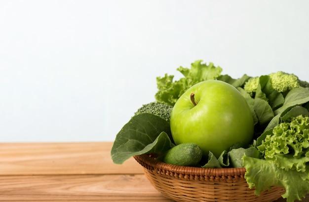 Chiuda sulla mela verde con la merce nel carrello di verdure verde mista