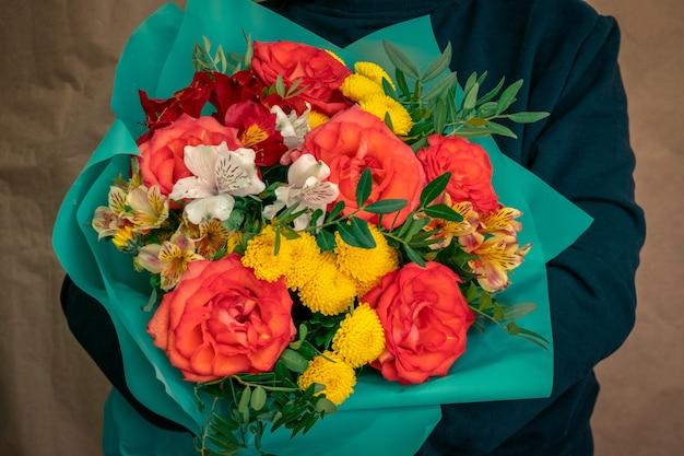 Chiuda sulla miscela luminosa del mazzo dei fiori freschi del giardino avvolti nel fuoco selettivo della carta del turchese