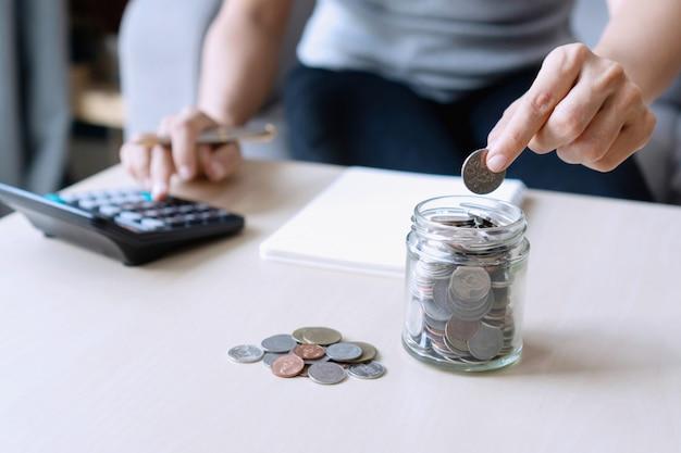 Chiuda sulla moneta della tenuta della mano per il risparmio dei soldi mentre per mezzo del calcolatore