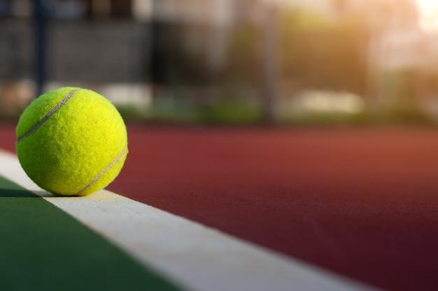 Chiuda sulla pallina da tennis sul fondo della sfuocatura della corte