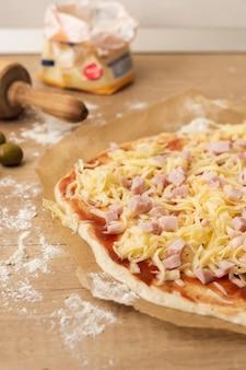 Chiuda sulla pasta della pizza con la mozzarella e il prosciutto della salsa al pomodoro