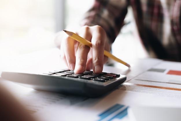Chiuda sulla penna della donna che indica il grafico del grafico in questo mese e usi il calcolatore per i piani per migliorare la qualità il mese prossimo.