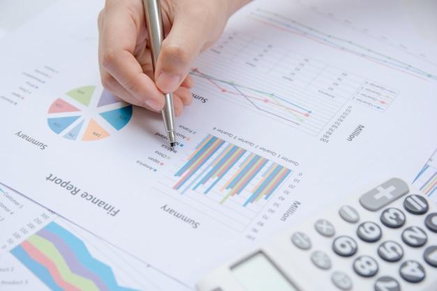 Chiuda sulla penna di tenuta della donna della mano che indica sul grafico di rapporto sommario e calcoli la finanza.