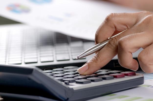 Chiuda sulla penna di tenuta della mano della donna di affari del fuoco molle e sul calcolatore del pulsante della stampa alla scrivania