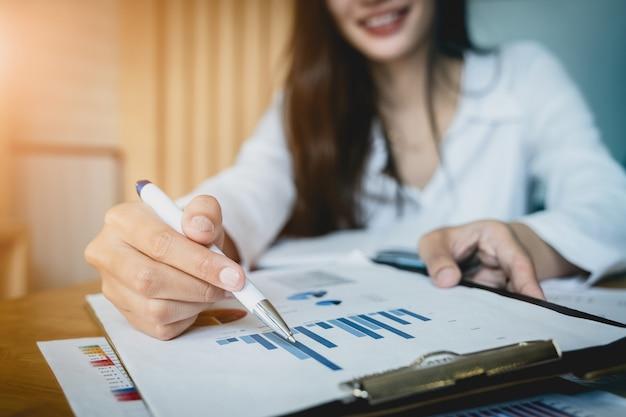 Chiuda sulla penna di tenuta della mano della donna di affari e sull'indicare al lavoro di ufficio finanziario.