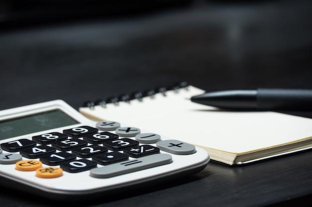 Chiuda sulla penna e sulla carta per appunti con il calcolatore sul fondo di legno dello scrittorio