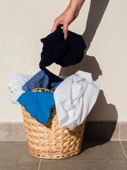 Chiuda sulla persona che mette i vestiti nel cestino di lavanderia