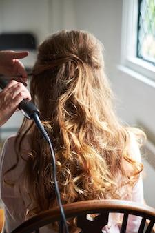 Chiuda sulla pettinatura di nozze della sposa con il bigodino di capelli elettrico