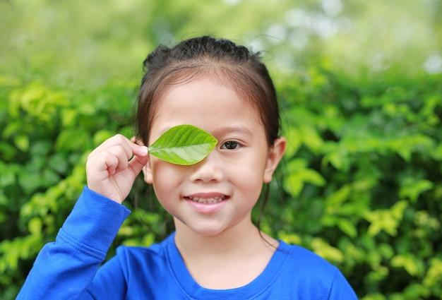Chiuda sulla piccola ragazza asiatica del bambino che tiene un occhio giusto di chiusura della foglia verde nel fondo verde del giardino.