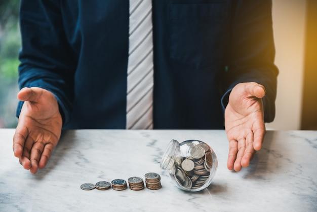 Chiuda sulla pila aperta della moneta dei soldi di mano dell'uomo d'affari con la moneta in vetro sulla tavola. concetto dei soldi di risparmio, concetto di contabilità di finanza