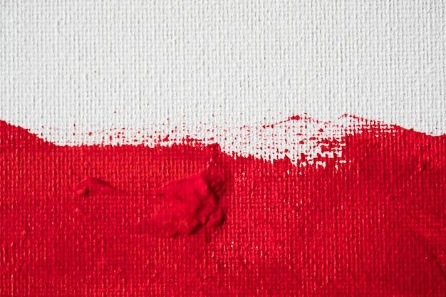 Chiuda sulla pittura di colore rosso di struttura su tela bianca