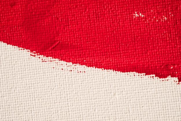 Chiuda sulla pittura di colore rosso di struttura sul fondo bianco della tela