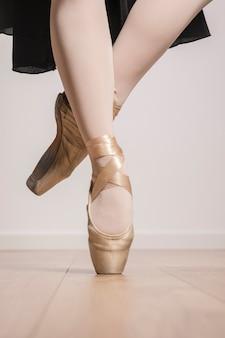 Chiuda sulla posa dei piedi in scarpe da punta