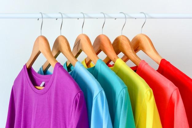 Chiuda sulla raccolta delle magliette variopinte dell'arcobaleno che appendono sulla gruccia per vestiti di legno nell'armadio o sulla cremagliera dell'abbigliamento