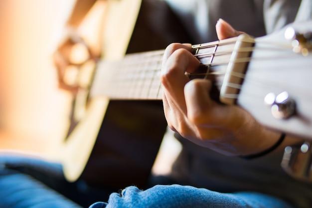 Chiuda sulla ragazza della mano che gioca la chitarra