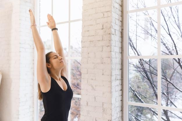 Chiuda sulla ragazza di yoga da solo nella stanza di yoga dalla finestra di mattina che sta con le mani su