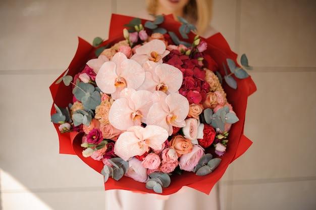 Chiuda sulla ragazza nel cappotto che tiene un mazzo di fiori rosa e rossi decorati con pianta