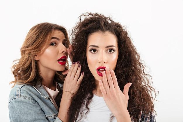 Chiuda sulla ragazza riccia sorpresa che copre la sua bocca mentre la sua amica che la parla in orecchio sopra la parete bianca