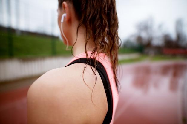 Chiuda sulla retrovisione della spalla della donna atletica mentre stanno sulla pista corrente.