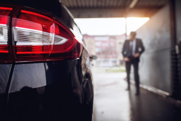 Chiuda sulla retrovisione delle luci dell'automobile alla stazione di self service di lavaggio manuale dell'automobile mentre il proprietario nel lavaggio del vestito.