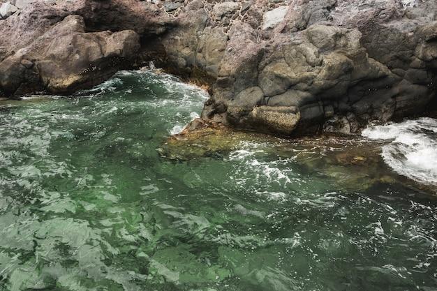 Chiuda sulla riva rocciosa commovente del mare