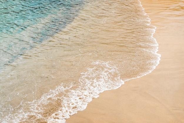 Chiuda sulla sabbia commovente dell'acqua di mare alla riva